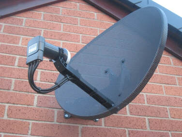 satellite dish fitted on a wall